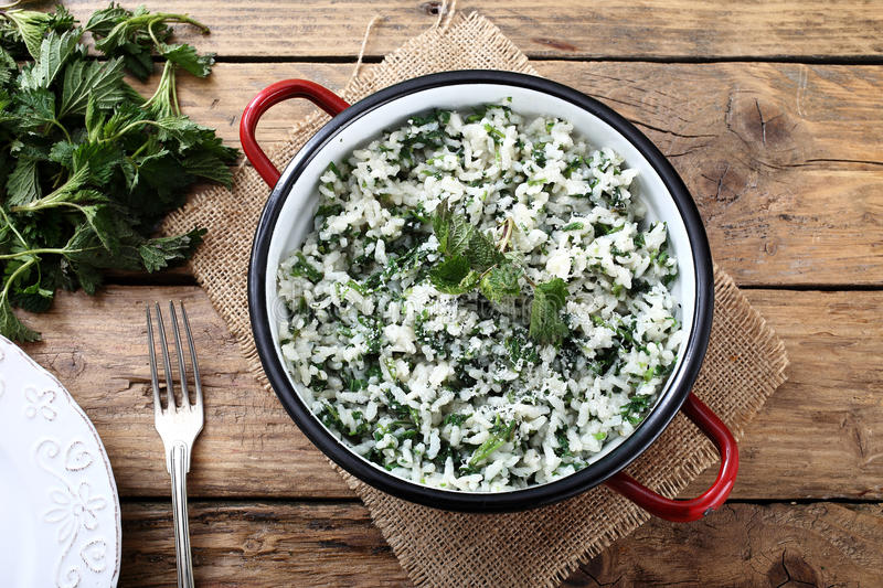 Rice with stinging nettles. Tea on kitchen rustic table background stock image