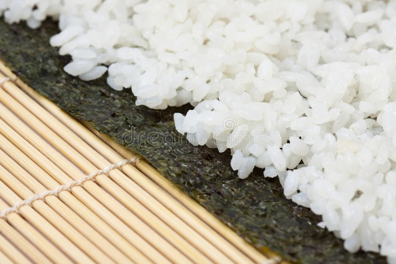 Rice on sushi nori. With a bamboo mat in the background stock images