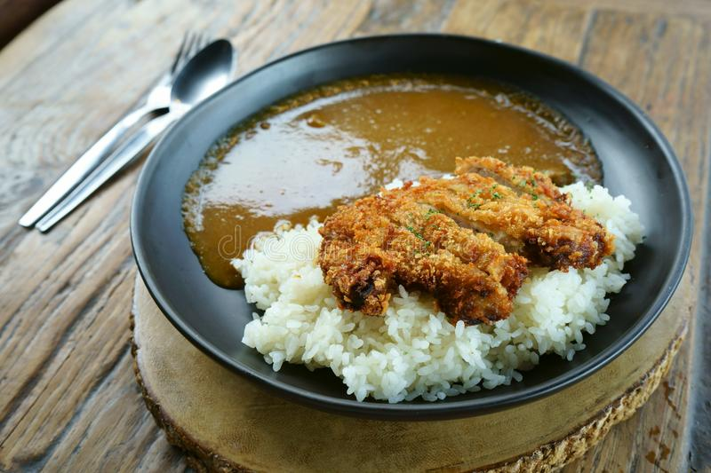 Rice on top with teriyaki fried chicken curry on wood table royalty free stock photos