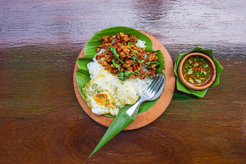 Rice topped with stir-fried minced pork and basil with Fried egg decorated with banana leaf and put on dark brown wood table. Top royalty free stock image