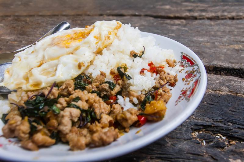 Rice topped with stir-fried pork and basil with fried Egg placed on the old wooden table as background. royalty free stock photography