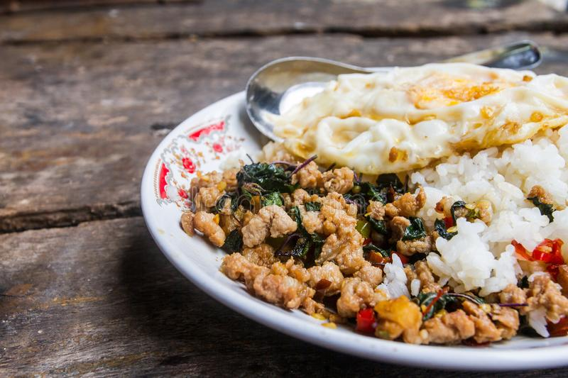 Close up Rice topped with stir-fried pork and basil with fried Egg placed on a table ready to be served. Which as The background royalty free stock image