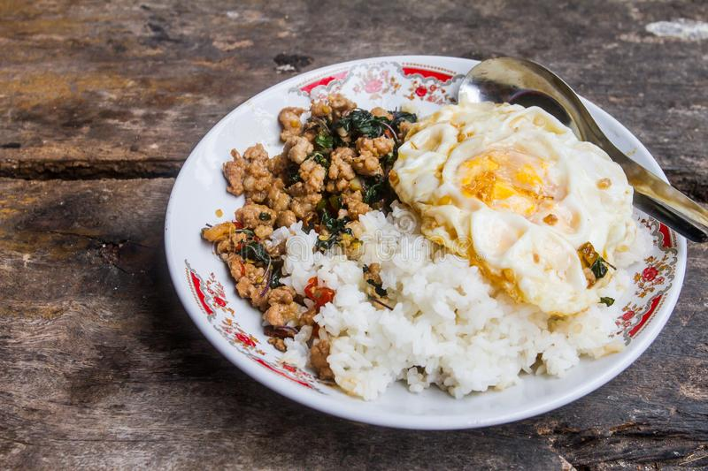 Rice topped with stir-fried pork with basil and fried Egg, placed on a wooden floor, which is the background. stock image