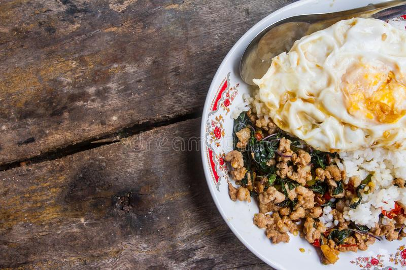 Rice topped with stir-fried pork and basil with fried Egg placed on old wood as the background. stock photo