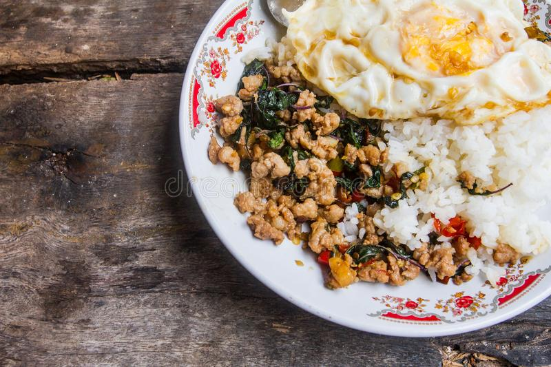 Rice topped with stir-fried pork and basil with fried Egg placed on a table ready to be served. Which as The background stock photo