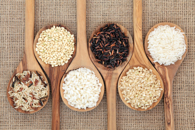Rice Varieties. In olive wood spoons over hessian background stock image
