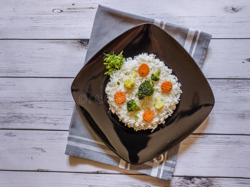 Rice with vegetable on black plate on white wooden background. Close up royalty free stock photo