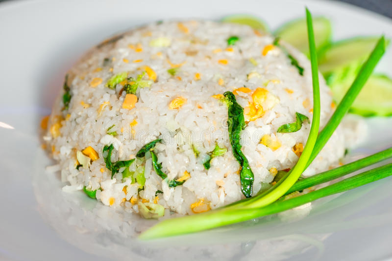 Rice with vegetables in a Thai restaurant close-up. On a white plate stock photos