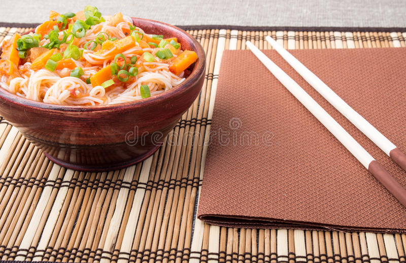 Rice vermicelli hu-teu in a small brown wooden bowl. Rice vermicelli hu-teu with vegetable carrot sauce in a small brown wooden bowl on a striped mat near stock image