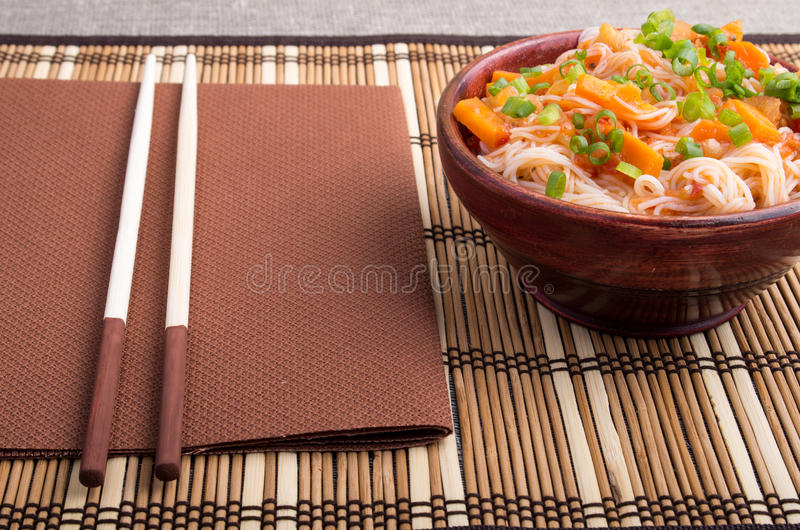 Rice vermicelli hu-teu with vegetable carrot sauce. In a small brown wooden bowl on a striped mat near chopsticks royalty free stock photography