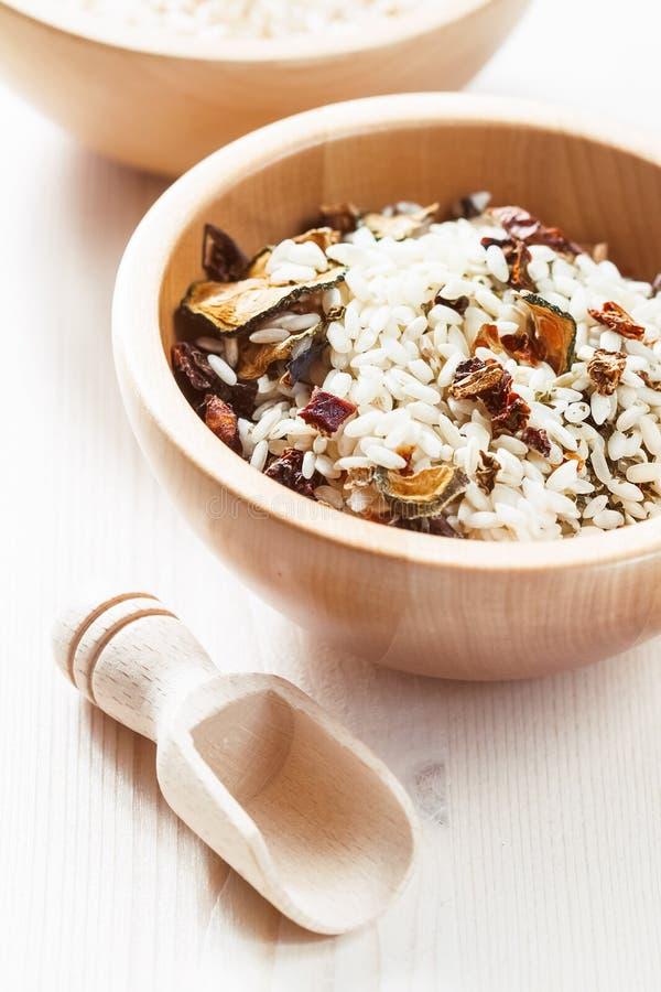 Rice w drewnianym pucharze z składnikami dla risotto obraz stock