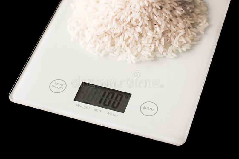 Rice on white kitchen scales on a black background royalty free stock image