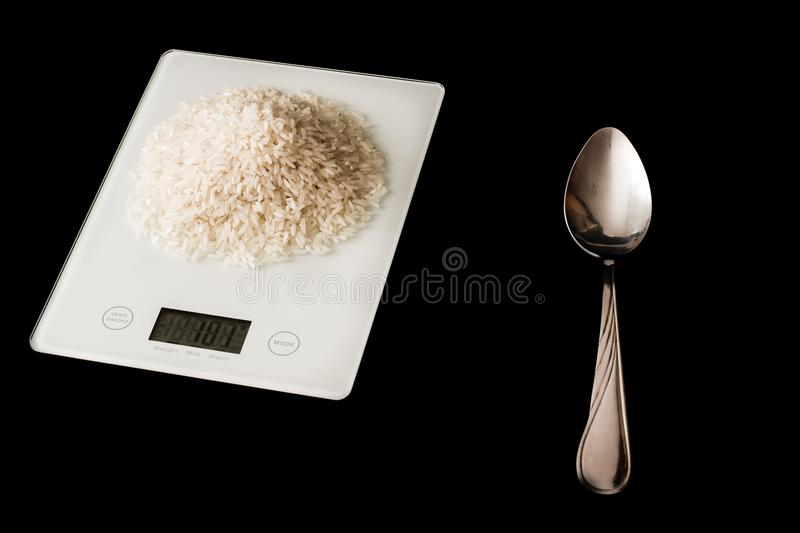 Rice on a white scales and a spoon stock images