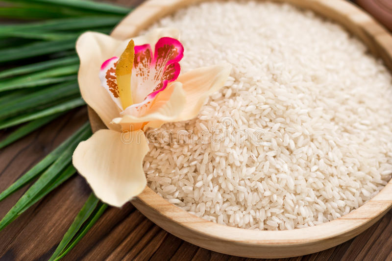 Rice in wooden plate and anise on brown wooden background. Rice and spices in ecological container. Set for cooking. Set for spa. stock image