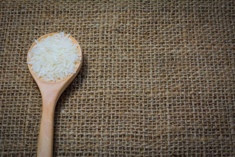 Rice z drewnianą łyżką na workowym tle obrazy royalty free