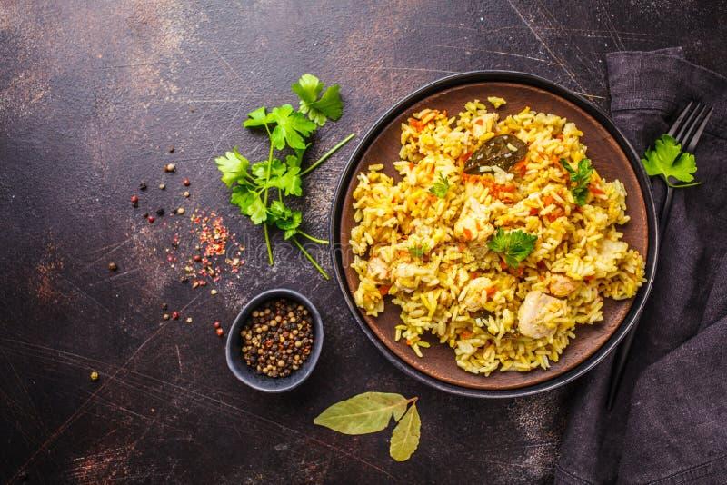 Rice z kurczakiem w czarnym talerzu na ciemnym tle, wierzchołek rywalizuje obrazy stock