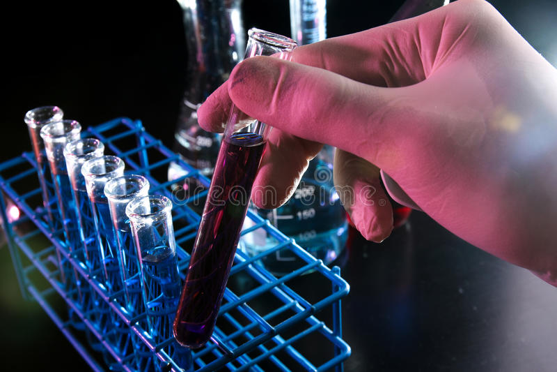Ricerca del laboratorio con la provetta della tenuta della mano immagine stock