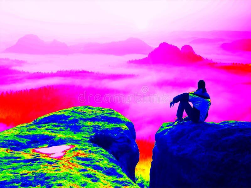 Ricerca infrarossa fantastica Turista stanco sul picco roccioso Alba meravigliosa in montagne, foschia arancio pesante a Valle pr fotografie stock libere da diritti
