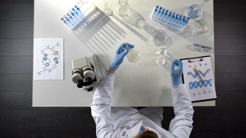 Ricercatore di biochimica osservando agente chimico in boccetta in laboratorio, topview immagini stock