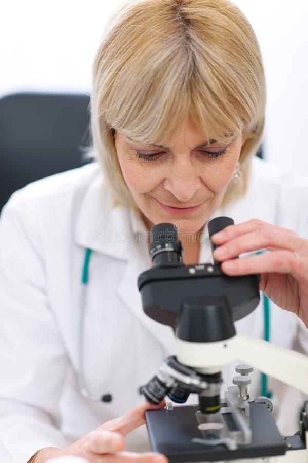 Ricercatore femminile maggiore che osserva in microscopio immagine stock