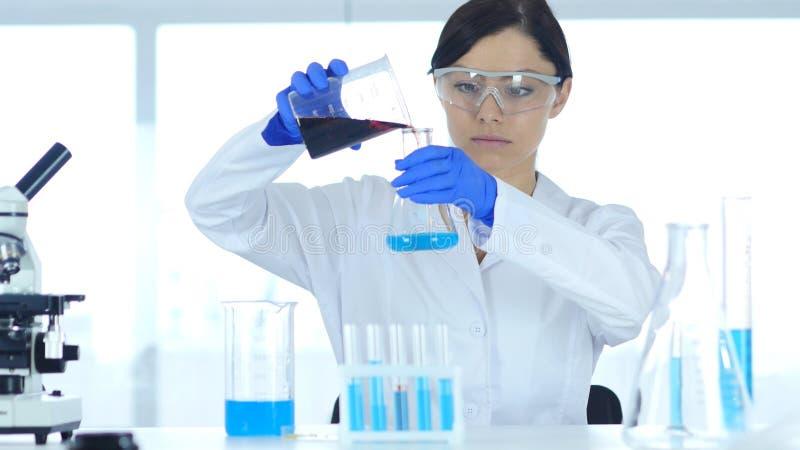 Ricercatore Pouring Chemical nella reazione di Flaskfor in laboratorio immagine stock