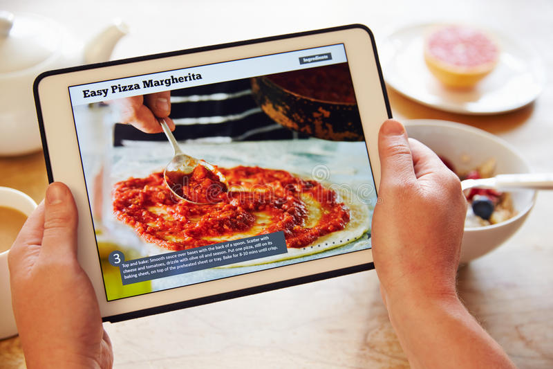 Ricetta App di Person At Breakfast Looking At sulla compressa di Digital fotografia stock libera da diritti