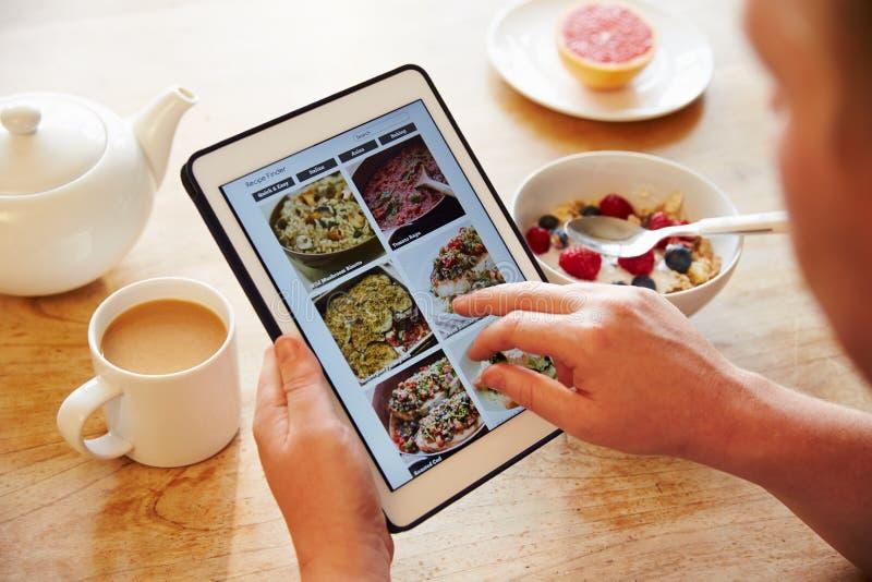 Ricetta App di Person At Breakfast Looking At sulla compressa di Digital immagine stock libera da diritti