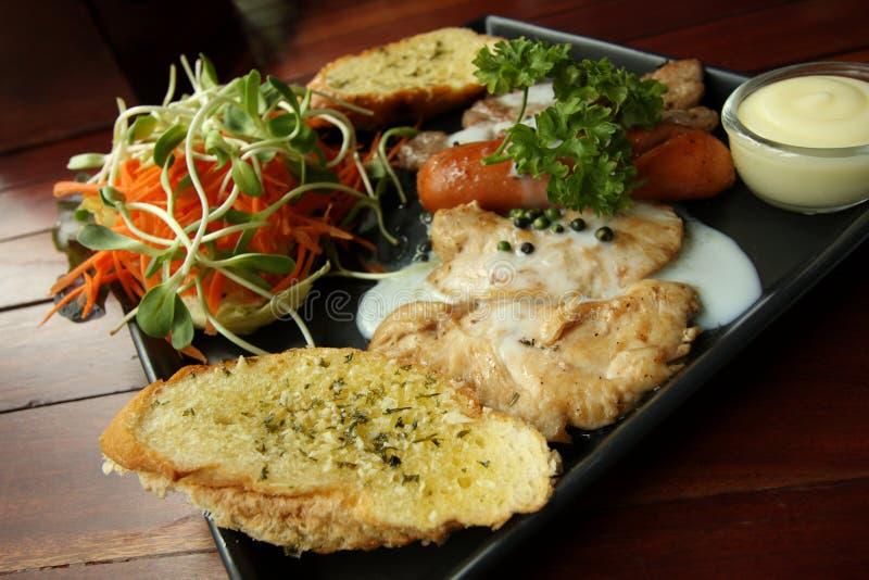 Ricetta arrostita delle bistecche, della salsiccia, del pane all'aglio e dell'insalata immagini stock