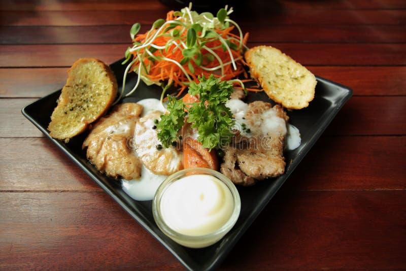Ricetta arrostita delle bistecche, della salsiccia, del pane all'aglio e dell'insalata immagine stock