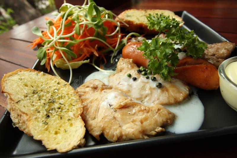 Ricetta arrostita delle bistecche, della salsiccia, del pane all'aglio e dell'insalata fotografie stock