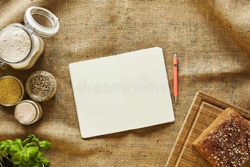 Ricette di scrittura in taccuino di scena del forno circondato dagli ingredienti per produrre pane immagine stock