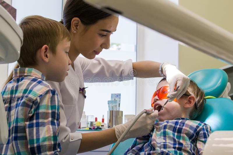 Ricezione all'odontoiatria Due ragazzi nel gabinetto Il dentista esamina la cavità orale fotografia stock