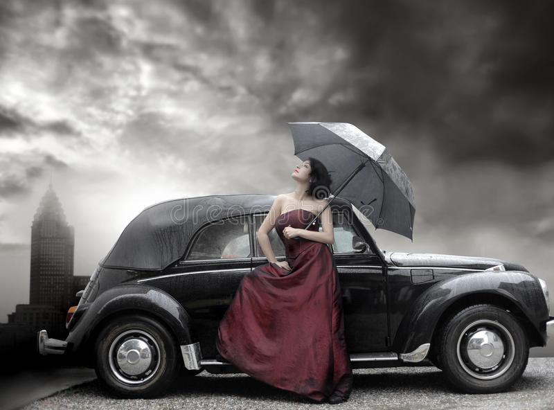 Rich. Lady in purple dress and holding umbrella next to vintage luxury car
