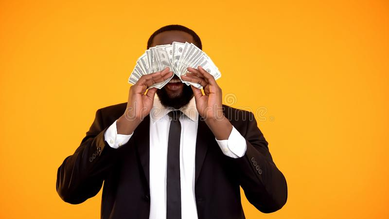 Rich afro-american man in formal suit closing eyes with dollar cash, easy money stock image