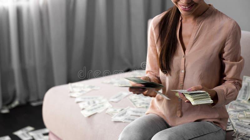 Rich Asian-Frau, die auf Couch sitzt und Geld, weiblichen Milliardär, Reichtum zählt stockfotografie
