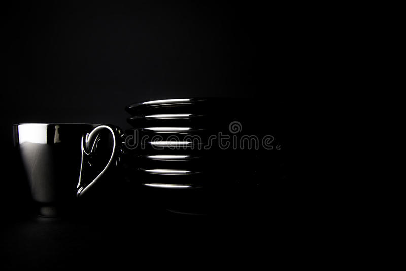 Rich black coffee. A single silver espresso cup by a stack of saucers isolated against a black background. The whole image is dark and luxurious reflecting the royalty free stock photography