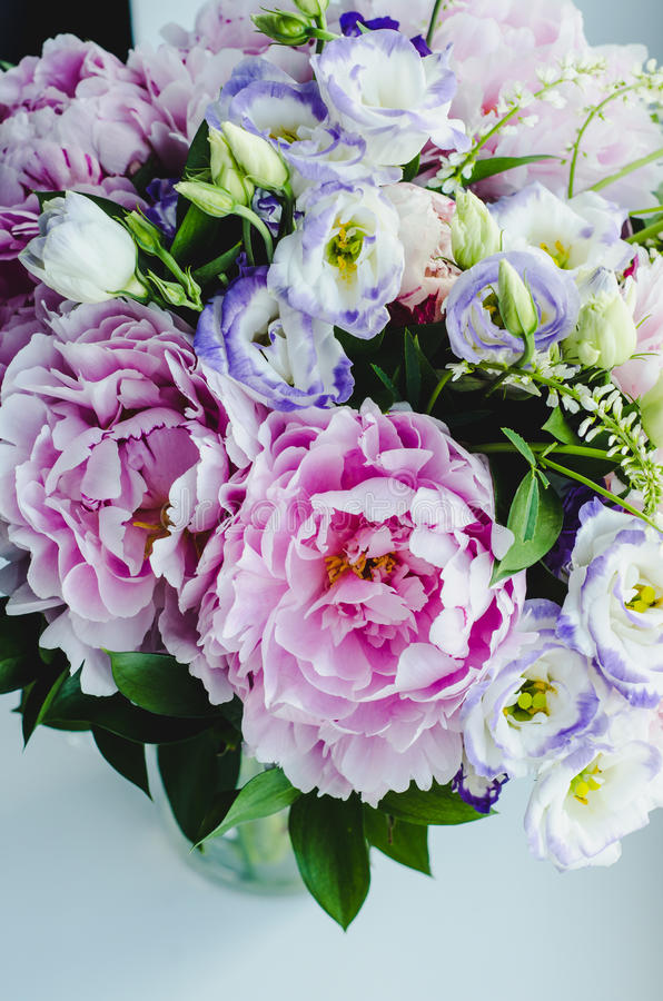 Rich bunch of pink peonies peony and lilac eustoma roses flowers in glass vase on white background. Rustic style, still life. Fresh spring bouquet, pastel royalty free stock photos
