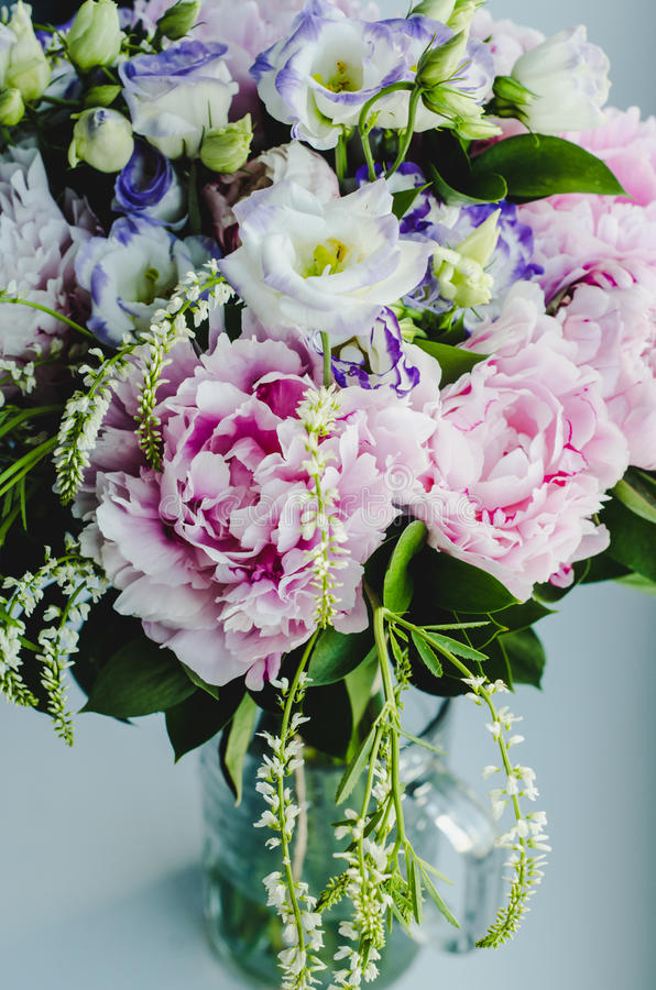 Rich bunch of pink peonies peony and lilac eustoma roses flowers in glass vase on white background. Rustic style, still life. Fresh spring bouquet, pastel royalty free stock image