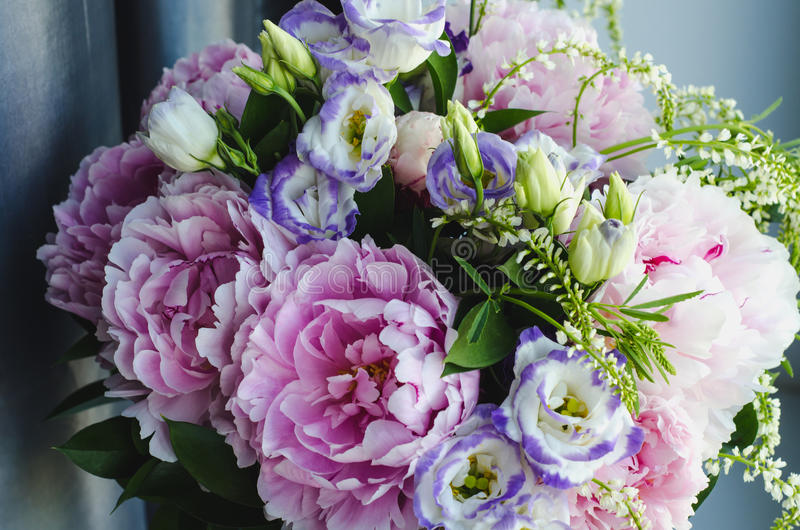 Rich bunch of pink peonies peony and lilac eustoma roses flowers. Rustic style, still life. Fresh spring bouquet, pastel. Colors. Summer Background. Tonal royalty free stock image