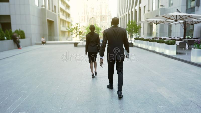 Rich business lady walking followed by bodyguard, successful lady, back view. Stock photo royalty free stock photography