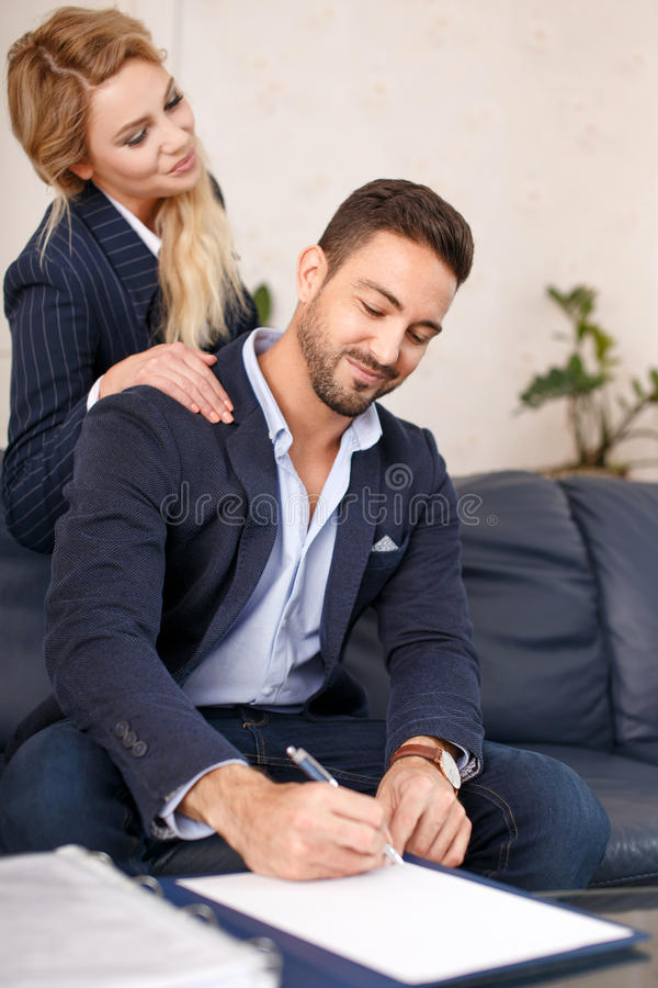 Rich businessman signing document to businesswoman stock photography