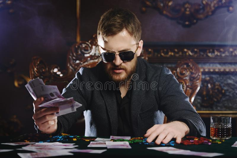 Rich casino player. Rich gambler man with the cards and chips in casino. Gambling, playing cards and roulette stock image