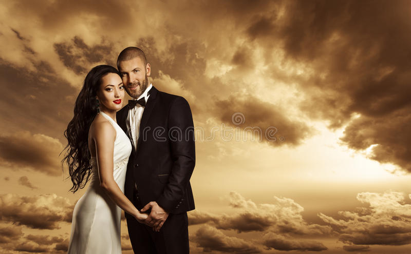 Rich Couple Portrait, Elegant Woman Dress and Man Suit Fashion. Rich Couple Portrait, Elegant Woman Dress and Man Suit with Bow Tie, Fashion Beauty over Evening royalty free stock image