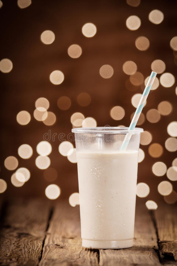 Rich creamy smoothie with festive party lights royalty free stock photography