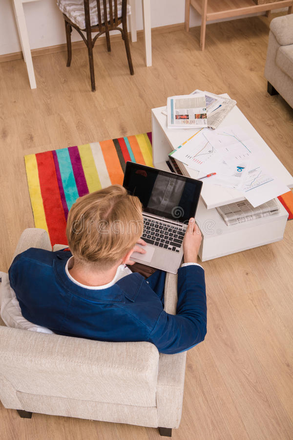 Rich European businessman working at home. Top view of rich European businessman working at home. Freelance man in business suit sitting with his laptop computer royalty free stock image