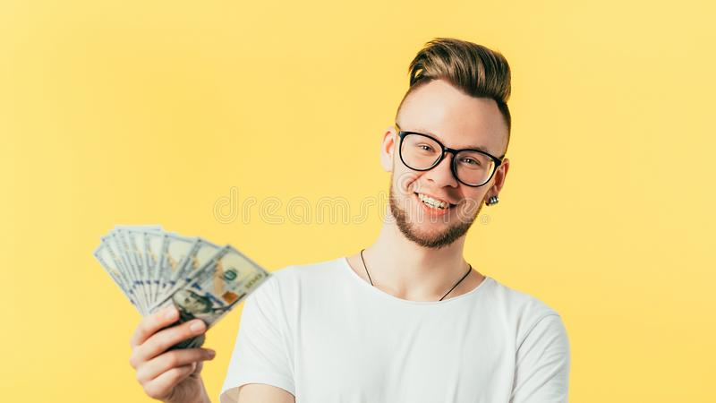 Rich generation successful millennial guy portrait. Rich generation. Portrait of successful millennial guy. Young hipster man in glasses holding money fan stock photo
