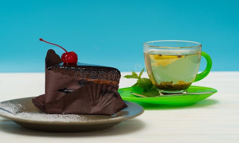 Rich glasade chokladkakan med kopp te arkivbilder
