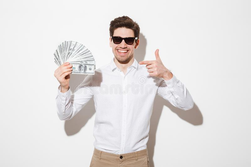 Rich and happy man in shirt and sunglasses rejoicing and pointing finger on lots of money dollar cash, isolated over white wall w stock images