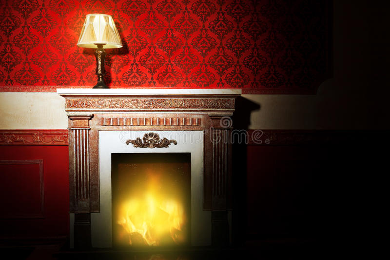 Rich interior with antique lamp and fireplace in red vintage room royalty free stock image