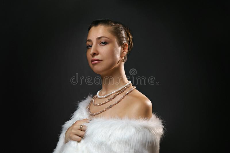 Rich lifestyle. Beautiful sexual woman wearing jewelery and white fur vest. Beauty, fashion stock image